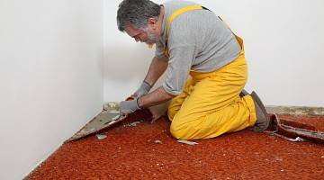 Male worker removing carpet