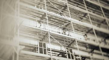 A black and white view of construction scaffolding on a building