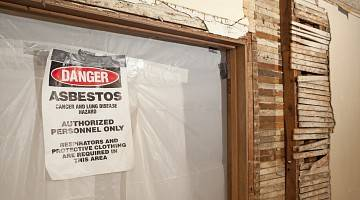 Sign on asbestos remove site warning of cancer and lung disease hazard due to asbestos exposure