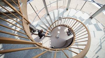 Top down view of man walking up spiral staircase