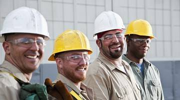 Four construction workers smile at camera
