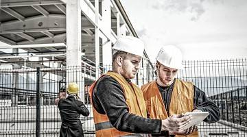 Two workers look over document at a large construction site