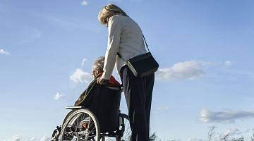 A professional woman pushes an older person in a wheelchair in the outdoors
