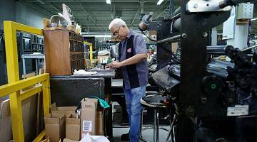Older man works in print shop