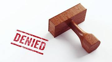 "Close-up of a rubber stamp and the word ""denied"""