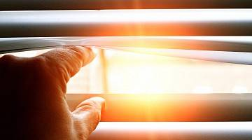 Close-up of fingers opening window blinds to let sun in