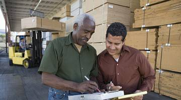 Two workers in a warehouse consult document