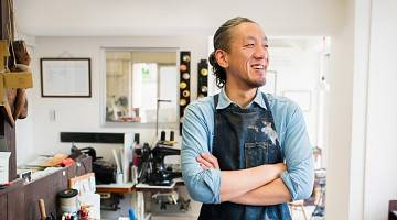 Japanese craftsperson stands in front of his workstation, smiling