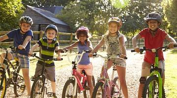 Five kids on bikes wearing bike helmets