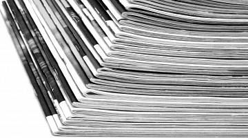 Black and white photo of stack of magazines