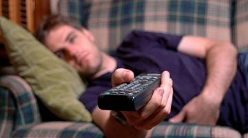 Young adult with remote in his hand, laying on couch watching television