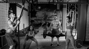 A black and white image of men and women lifting weights