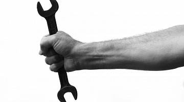 A black and white image of a wrist gripping a tool