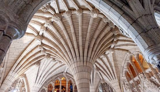 Stone arches and stain glass windows in the interior of the Canadian Parliament