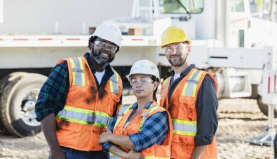 Three construction workers smile for the camera