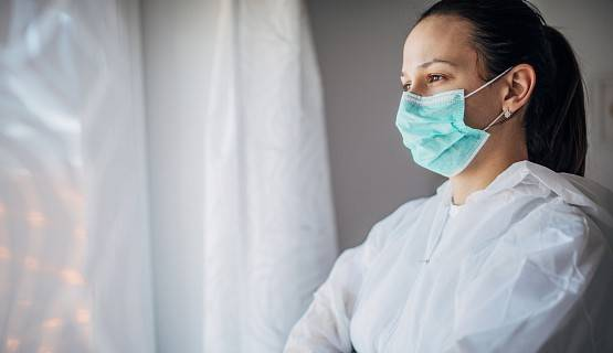 A health-care worker wearing a face mask and body covering