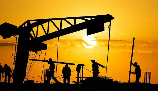 Silhouettes of construction workers against an orange sky