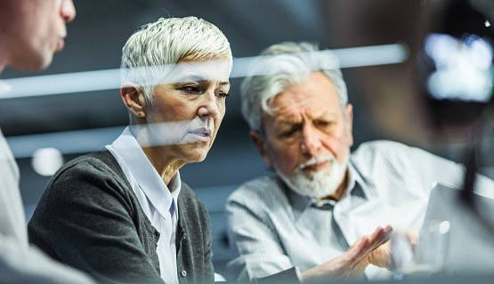 Two grey-haired workers have a discussion