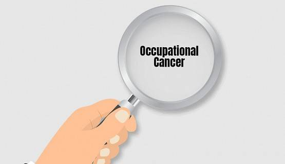 Hand holding magnifying glass over words occupational cancer
