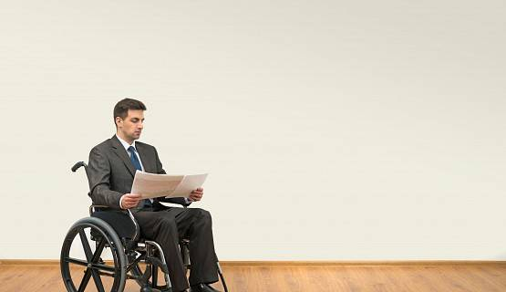 A man in a wheelchair reviewing documents